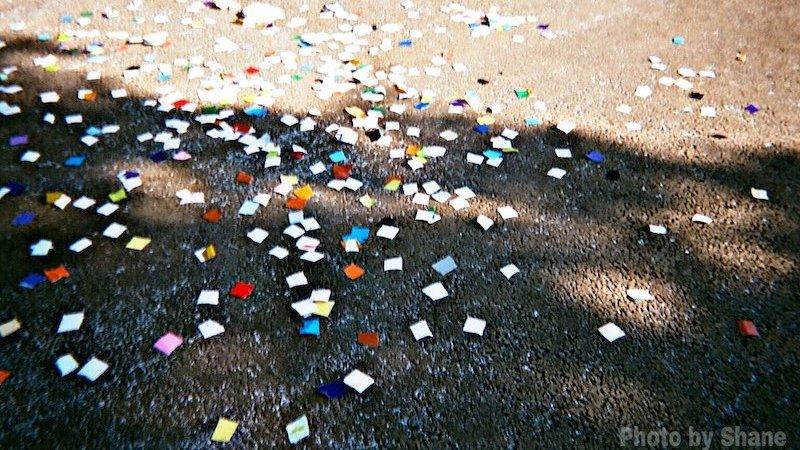 色紙が地面に撒き散らされている写真